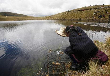an andean woman drinks water from the cortada